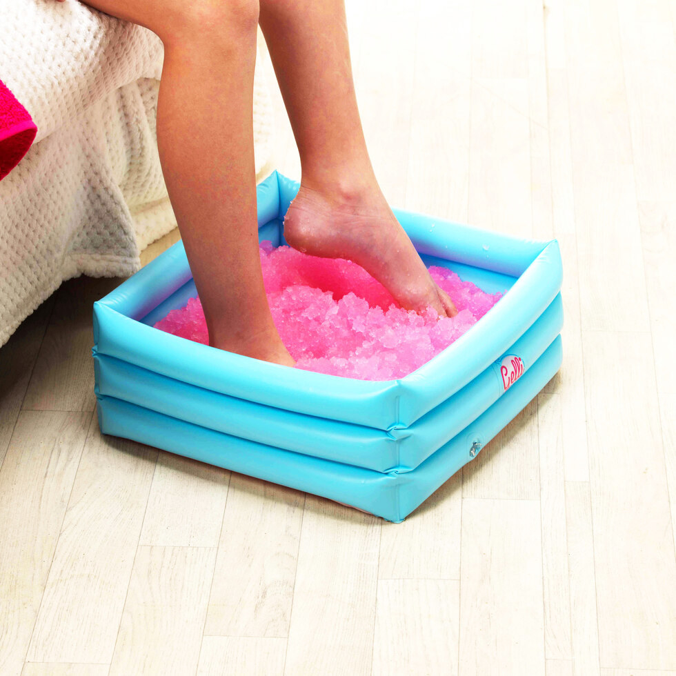 A person puts their feet in a small square inflatable tub filled with pink jelly