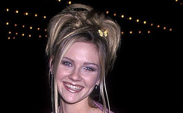 Kirsten Dunst with a messy up do hair style and butterfly clip in hair