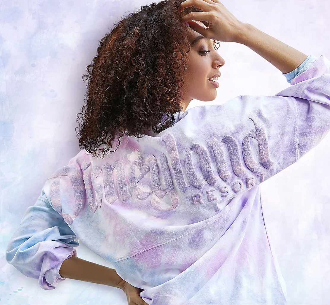 """A person facing backwards wearing a pastel pink, purple, and blue tie-dye oversized long-sleeved jersey that has the words """"Disneyland Resort"""" on the back in puff ink"""
