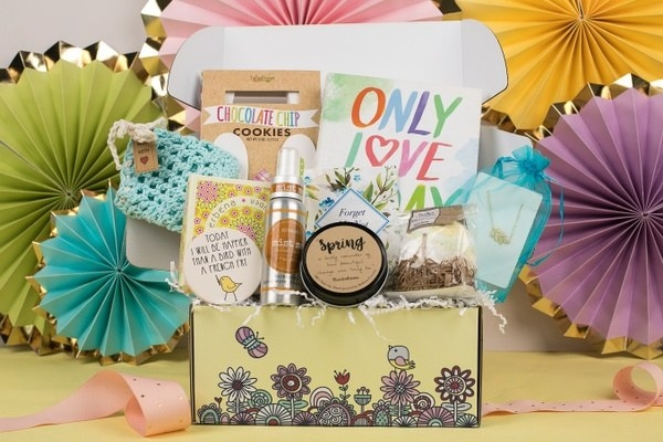 box filled with products like chocolate chip cookies, a card, a book, and more