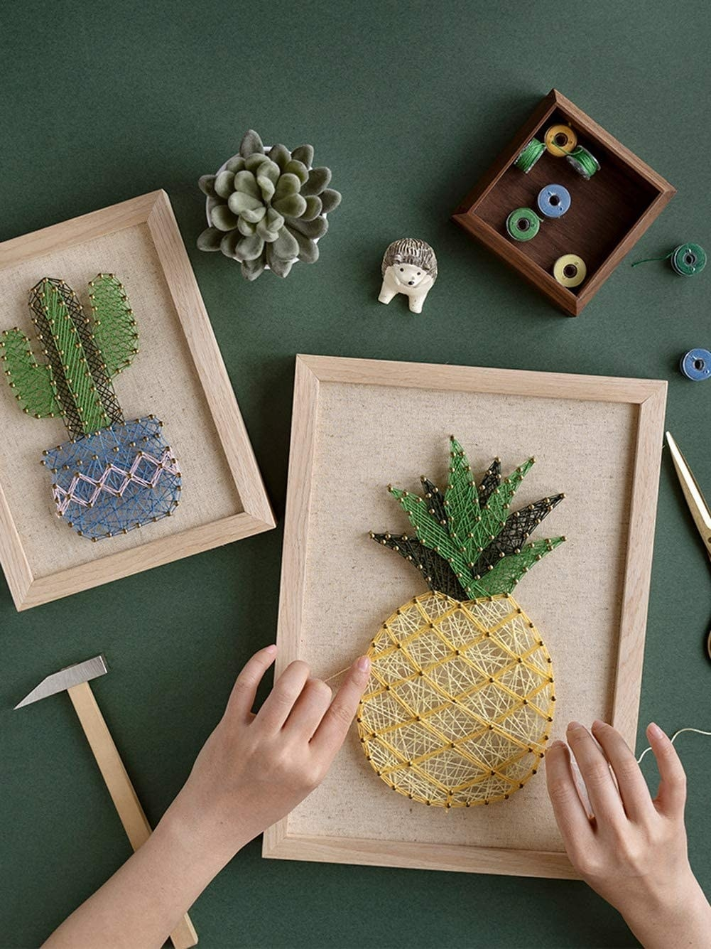 A person using pegs and string to create a pineapple image within a wooden frame