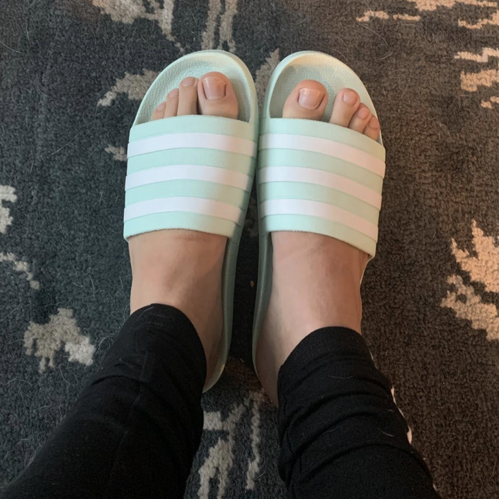 reviewer wears light blue and white stripe Adidas slides on feet