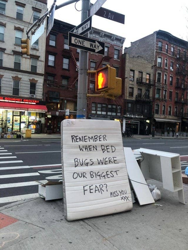 """A mattress on the sidewalk with the words, """"Remember when bed bugs were our biggest fear? miss you xxx"""" written on it"""