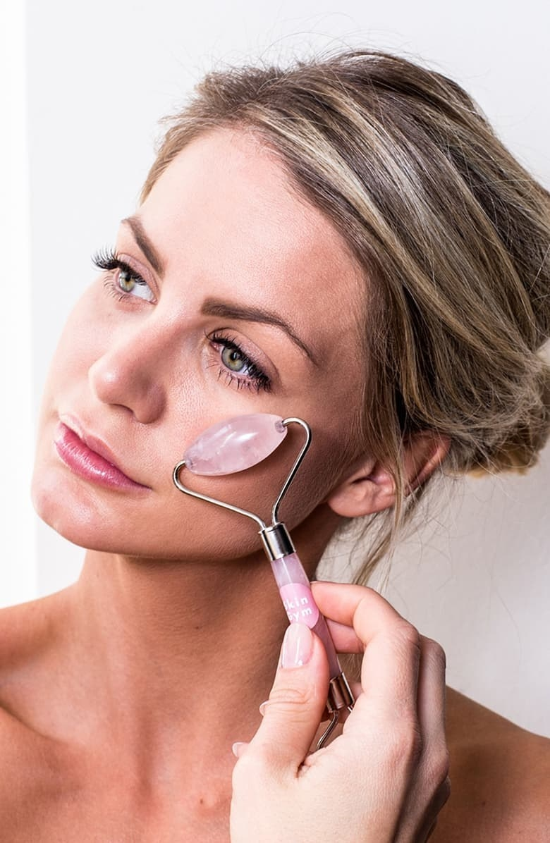 A model using the roller on their cheek