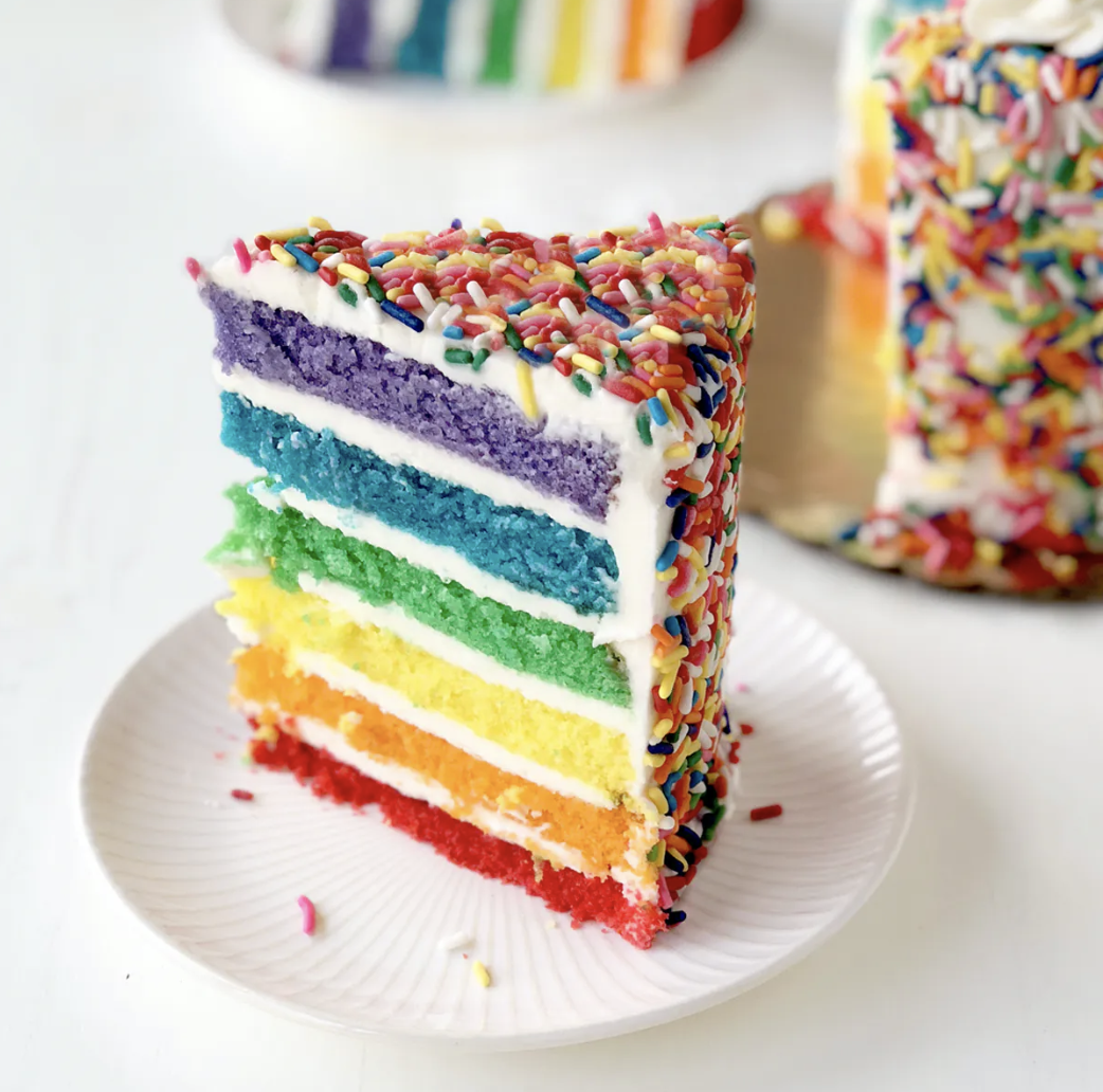 A slice of cake cut to show rainbow layers inside and rainbow sprinkles outside