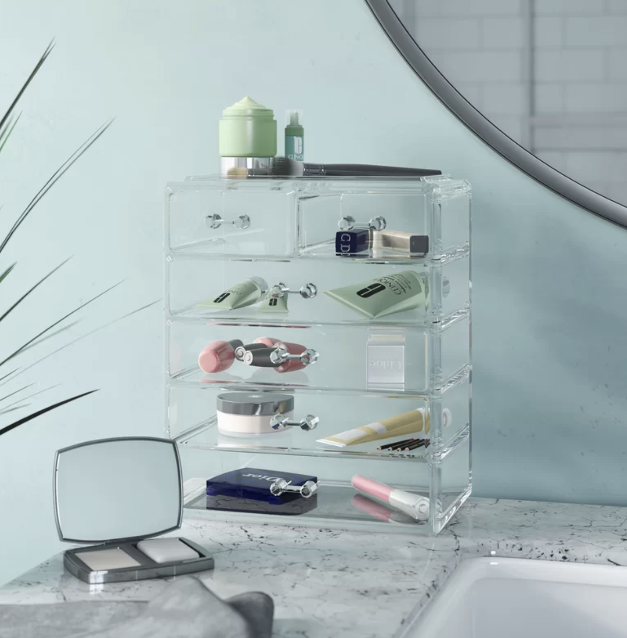 Clear rectangle cosmetics organizer filled with various makeup products on a marble bathroom countertop