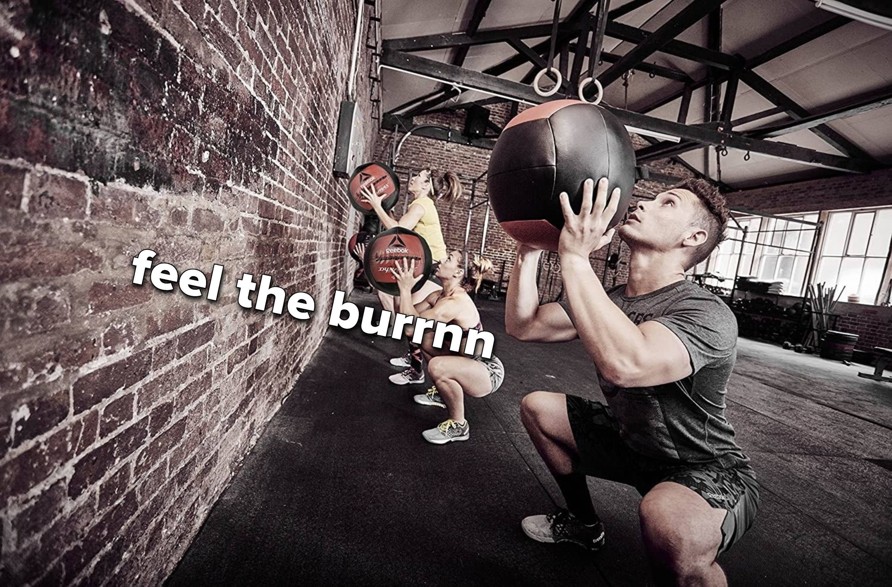 A line of people, squatting while holding medicine balls above their heads