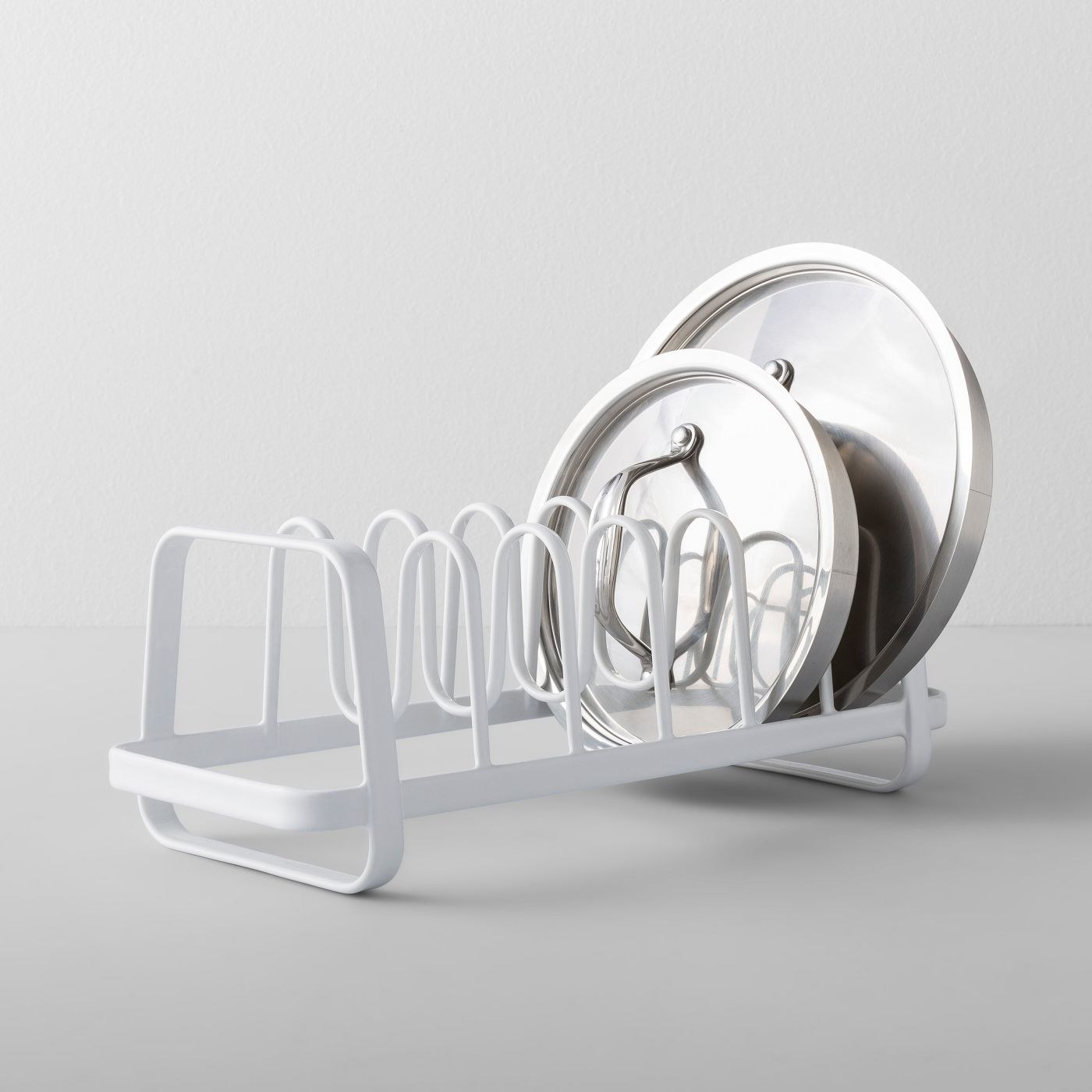 The lid holder with six compartments and two pot lids in it