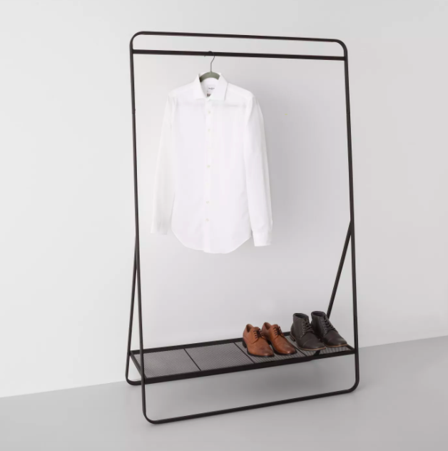 A metal rack with a rod across the top of the frame, and a shelf at the bottom