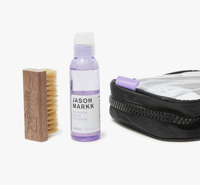 Purple cleaner bottle filled with clear solution next to brush and bag