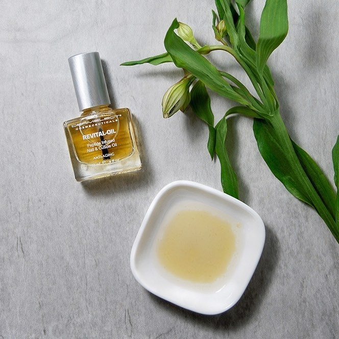 A bottle of nail oil next to a fresh sprig of flowers