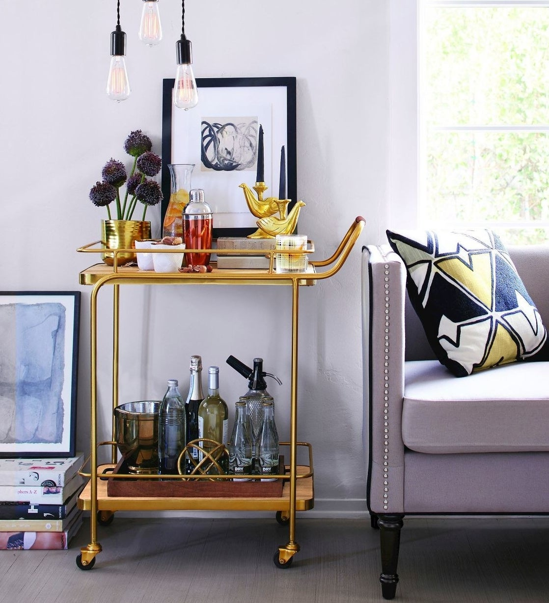 Gold bar cart with bottles and bar supplies on it