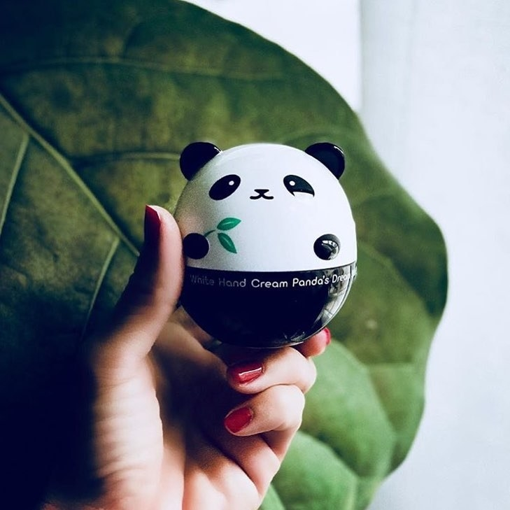 A hand holds a round cream that looks like a panda