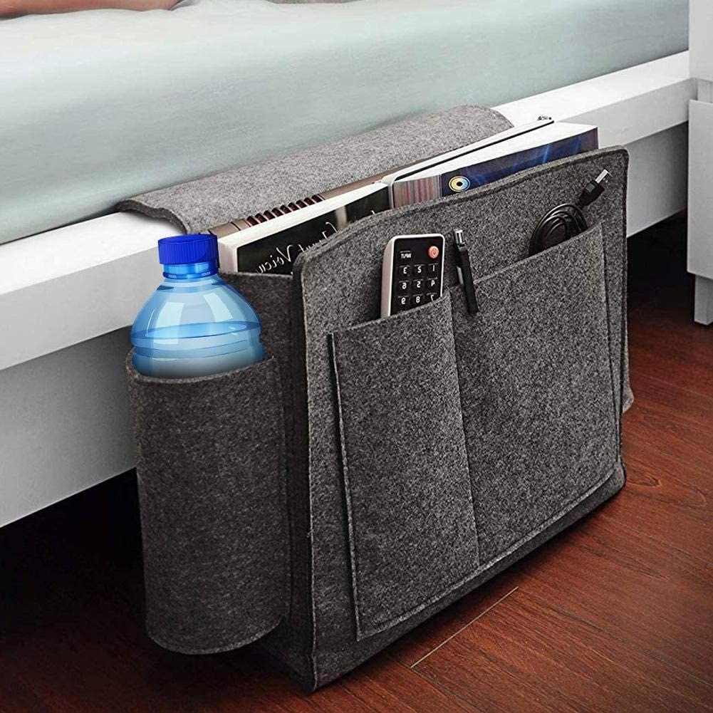 Felt bed caddy with water bottle, tv remote, pen, usb cable and books, hanging from bed frame