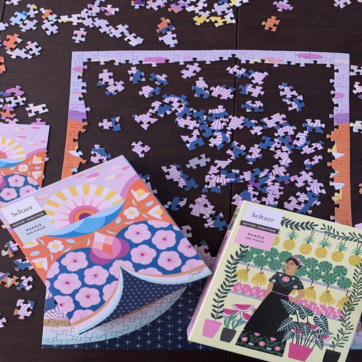 Colorful purple and pink flower puzzle on table next to fruit lady design puzzle