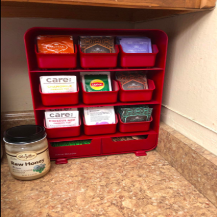 reviewer pic of a red plastic vertical organizer with removable compartments for filing tea bags