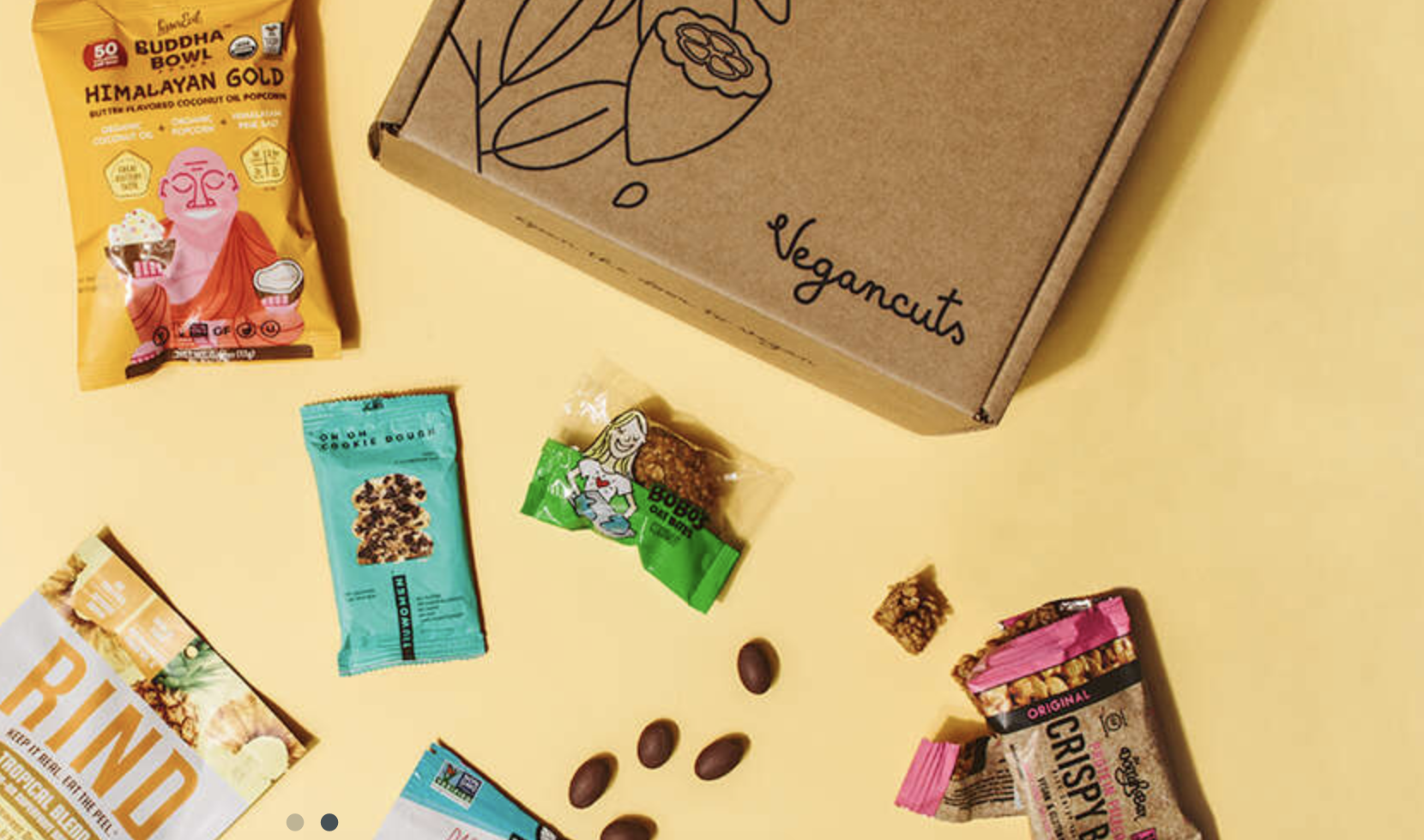 A Vegan cuts subscription box next to assorted vegan popcorn and snack bars