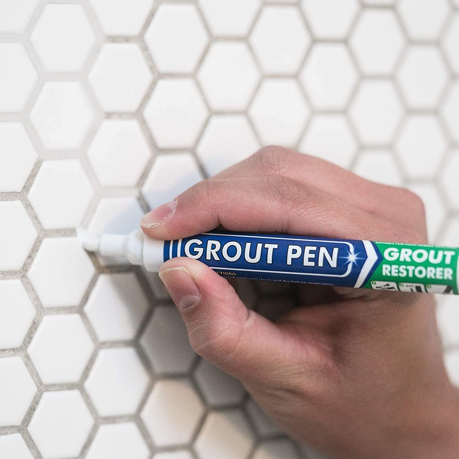 the pen cleaning grout between white tiles