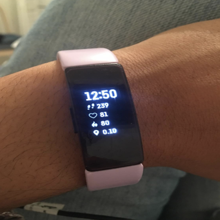 reviewer wears rose gold Fitbit on wrist