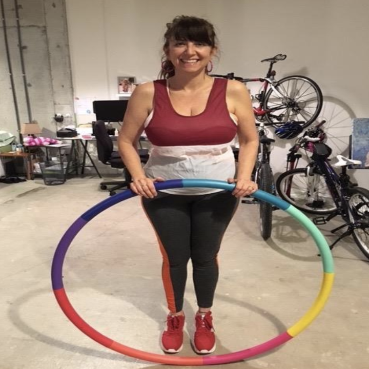 reviewer holds same weighted hula hoop in their garage