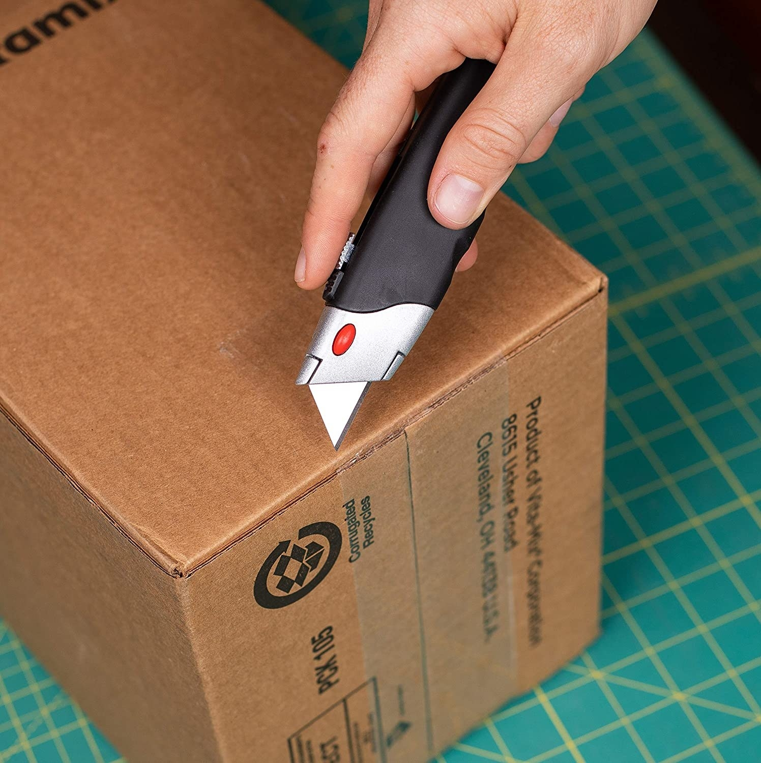 A box cutter with the blade extended about to cut some cardboard boxes