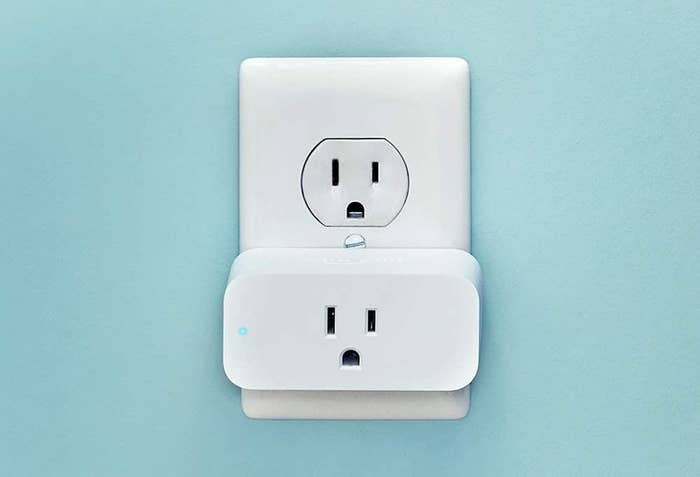 A white smart plug in a wall electrical outlet