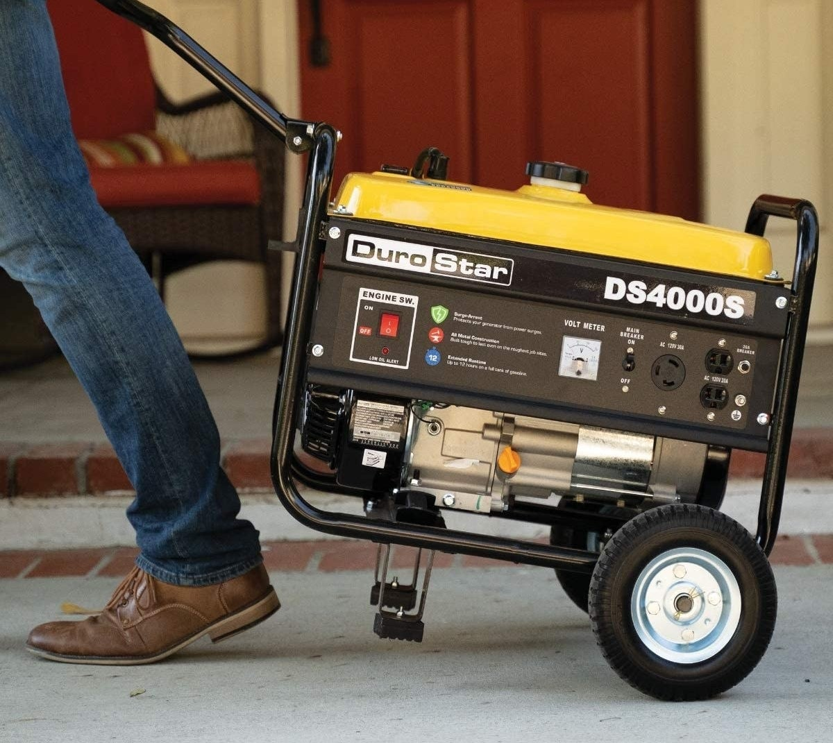 A black and yellow portable generator being wheeled by an individual wearing blue jeans and brown shoes