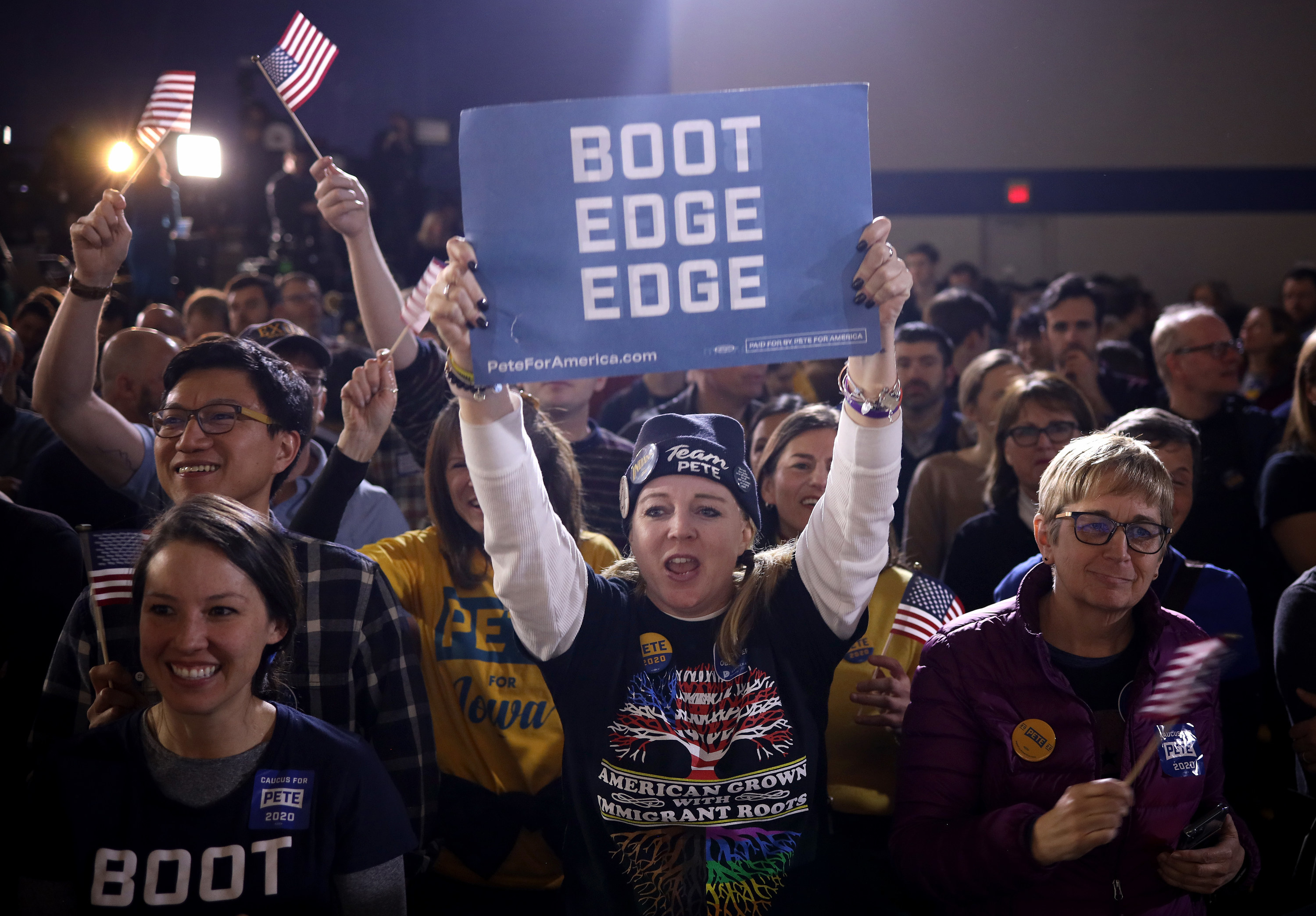 "A woman at a campaign rally holding up a sign that says ""boot edge edge"""