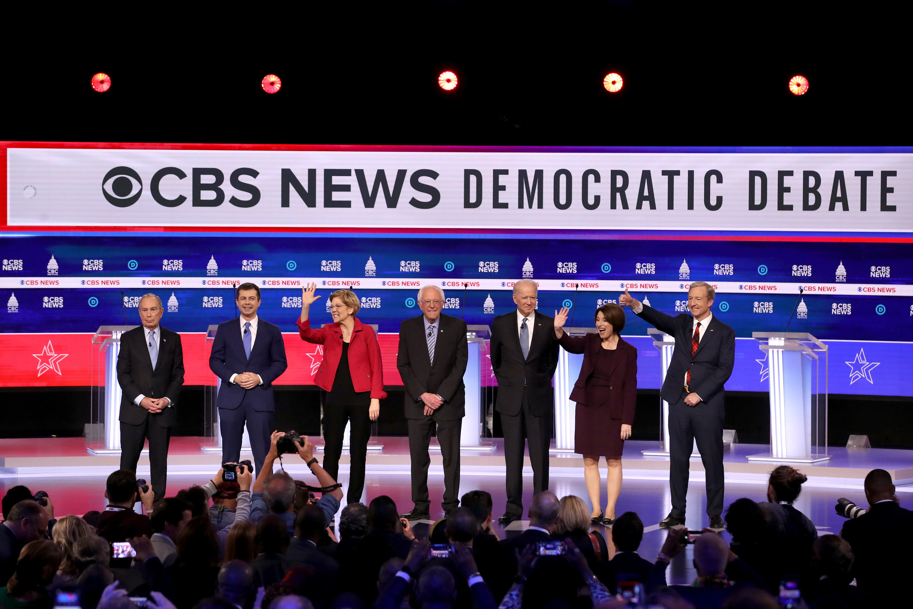 Seven Democratic presidential candidates standing on the debate stage