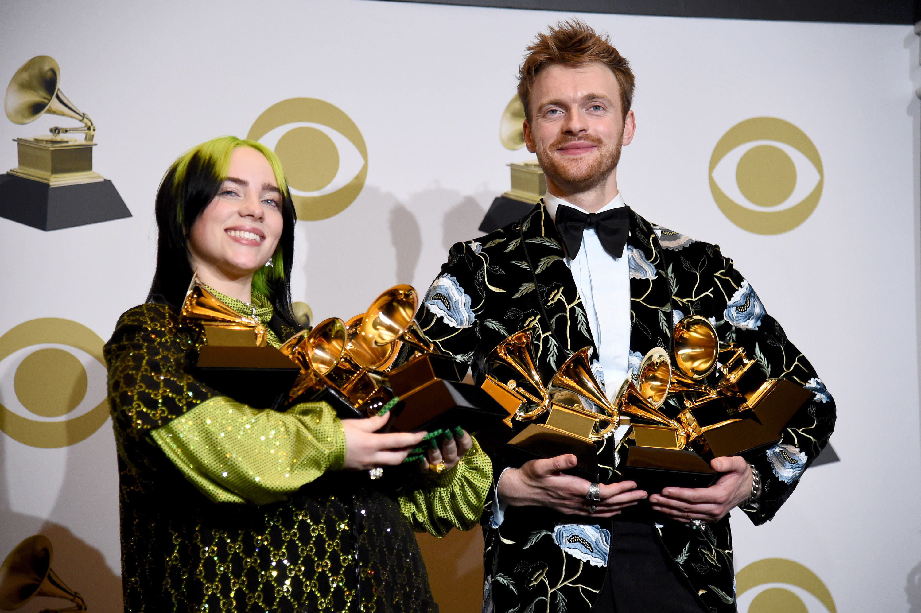 Billie Eilish and her brother cradling several Grammy's in their arms