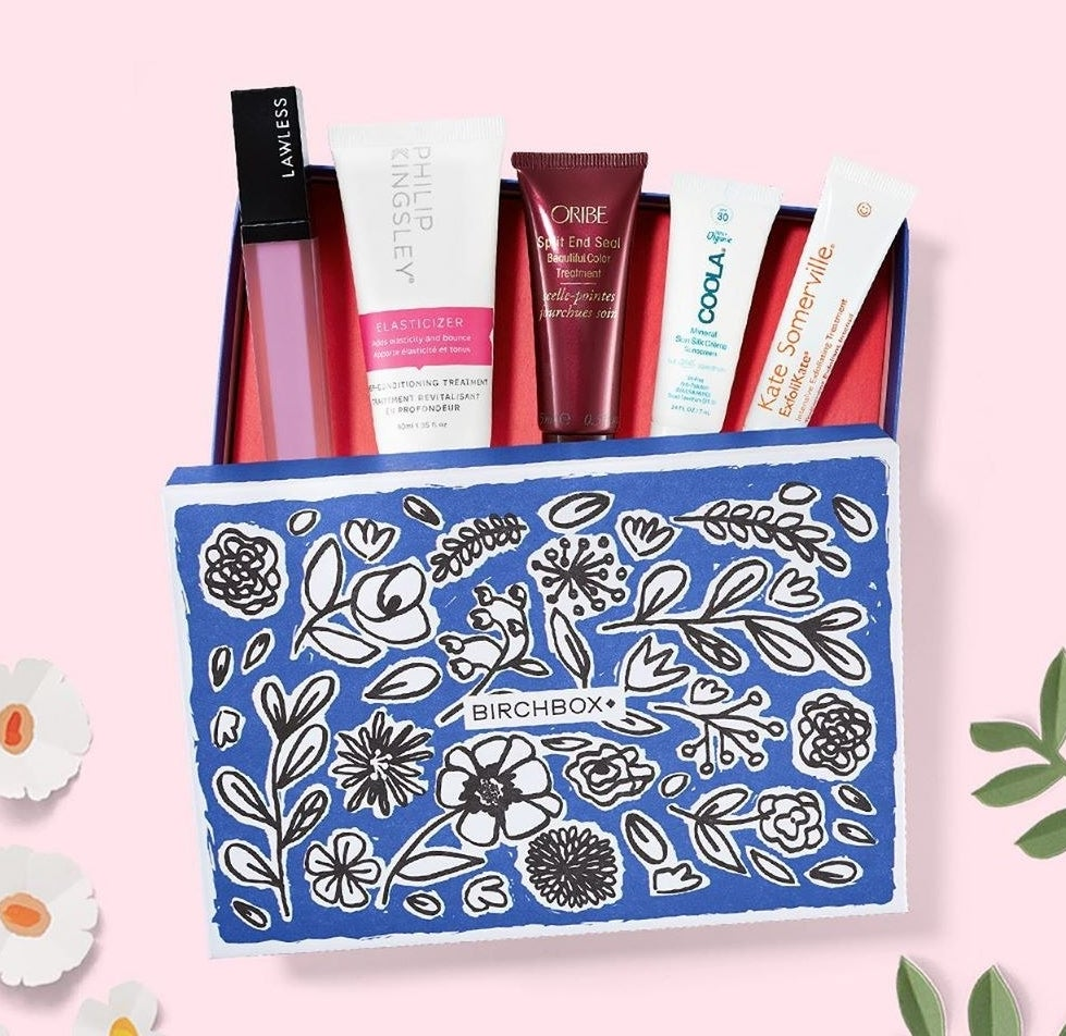 A blue floral Birchbox box with five samples peeking out from it, including a lipgloss and several skincare products.