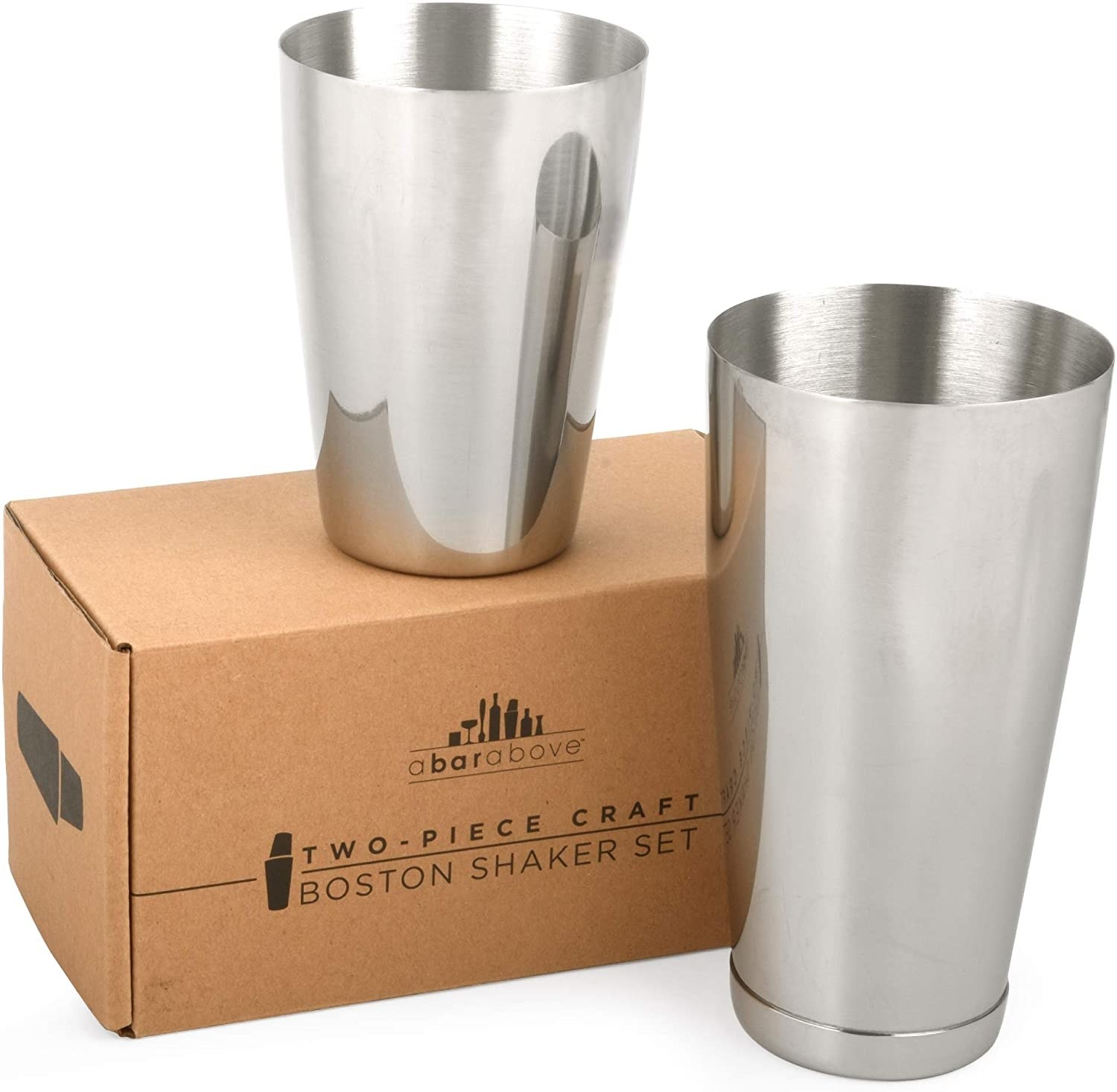 Two stainless steel drink shakers standing near and on top of the cardboard box they come in