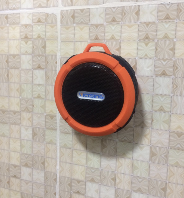 an orange circular speaker attached to a bathroom tile wall