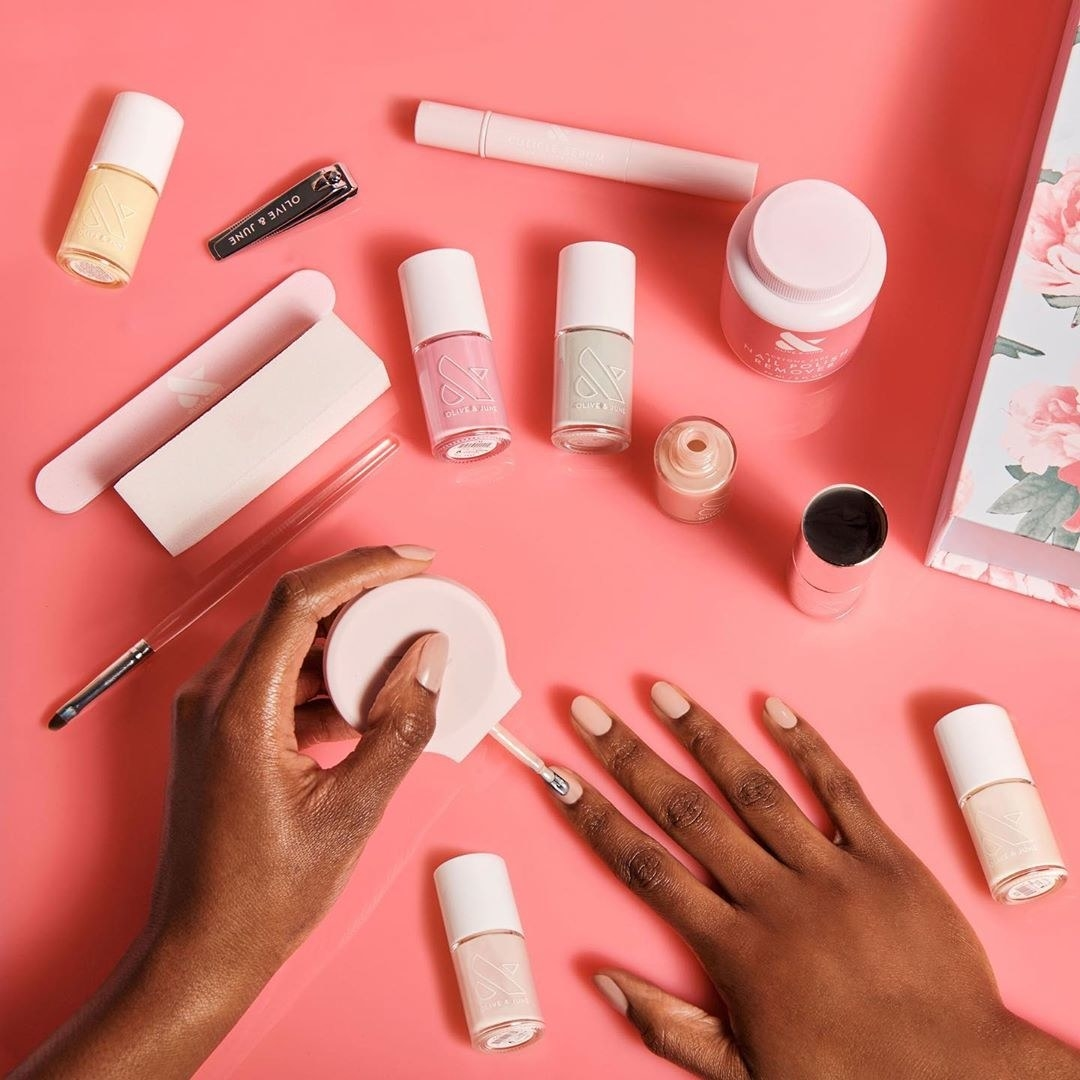 hands painting their nails while surrounded with items from the mani kit