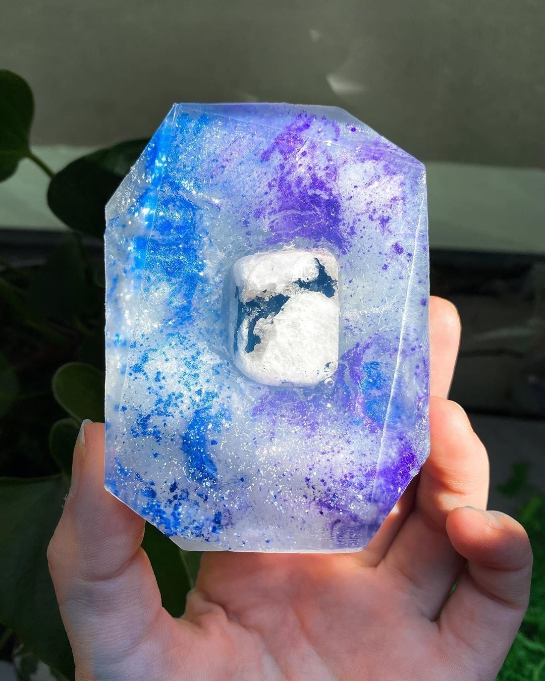 a clear bar of soap with purple and blue sparkles throughout and a crystal stone in the mdidle