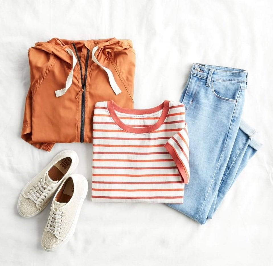 flatlay with an orange hoodie, striped tee, jeans, and white sneakers.
