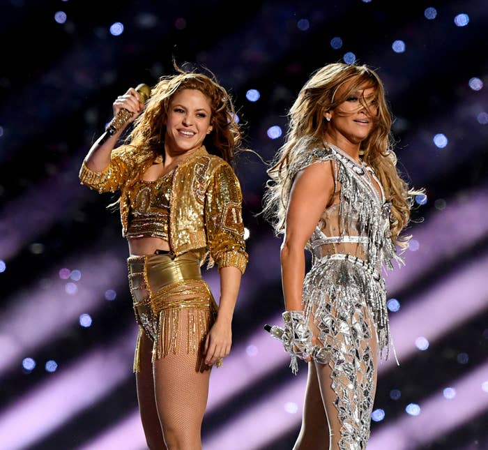 Shakira and Jennifer Lopez on stage dancing. They are happy