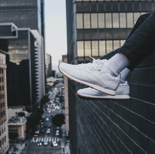 Minimalist leather sneakers on feet dangle over the edge of a city building, with view of the street below