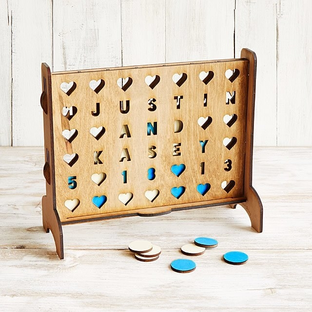"""the connect four-like game with some of the holes spelling out """"justin and kasey 5-18-13"""""""