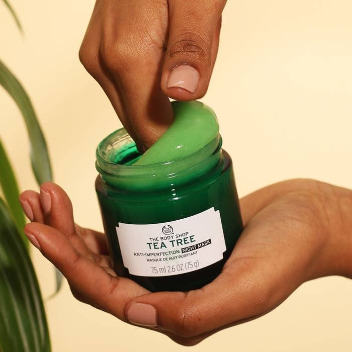 hand dipping into green jar of product
