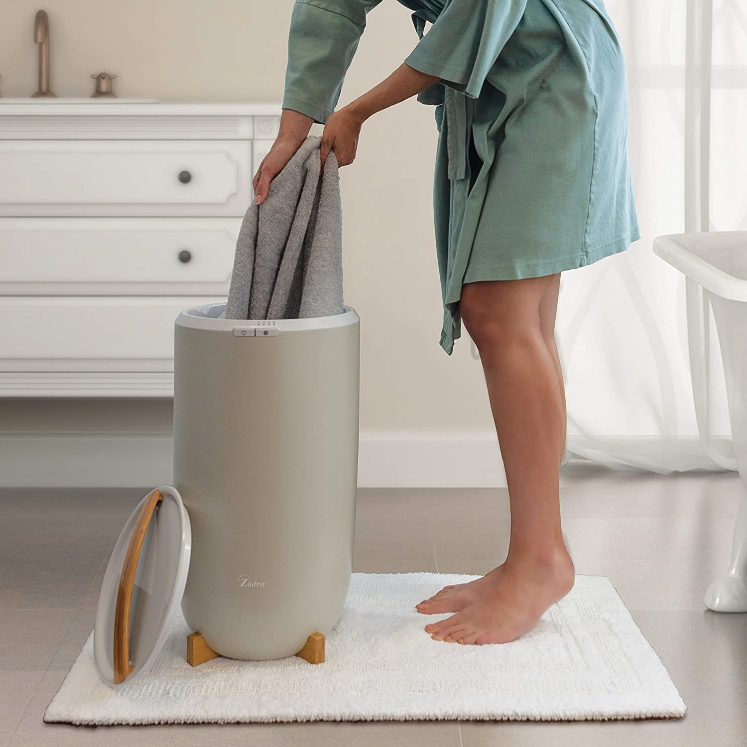 Person pulling towels out of upright towel warmer