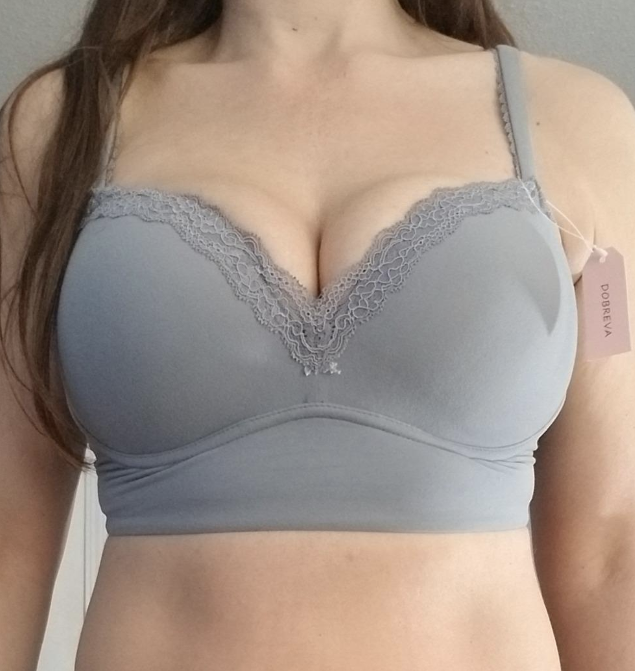 reviewer wearing the bra in gray with a sweetheart top shape, lace along the top of the bra, and a thick supportive band underneath the cups
