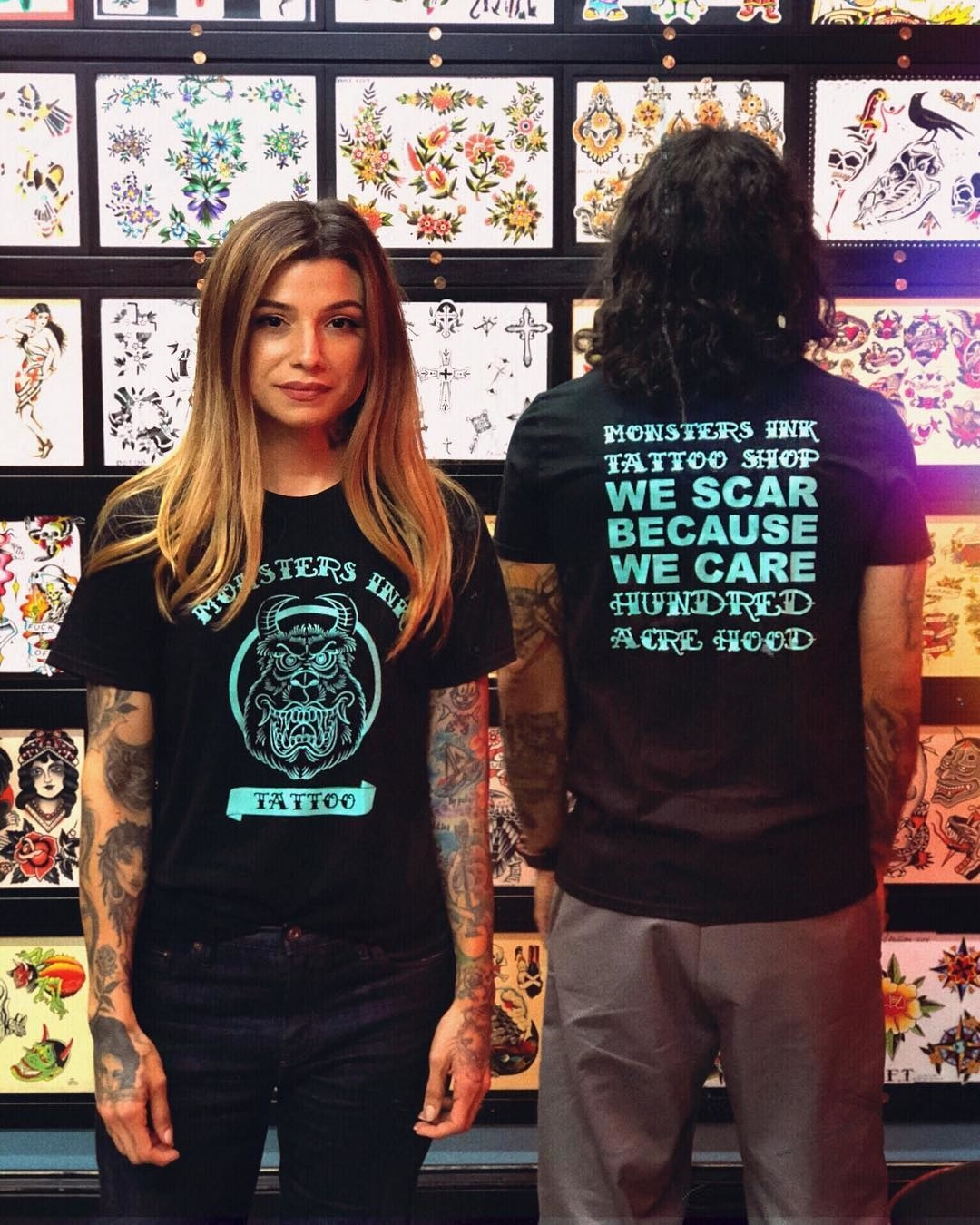 "two models: one is is showing the front of the shirt in black with a monsters ""ink"" logo and a scary version of sully, the other shows the back that says ""monsters ink tattoo shop we scar because we care"""