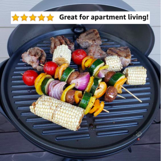 The grill with corn, steaks, and veggie kabobs cooking