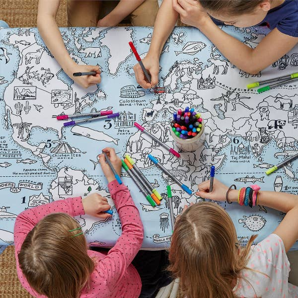 Children color on the tablecloth. It's light blue with white, uncolored countries and various things related to each region