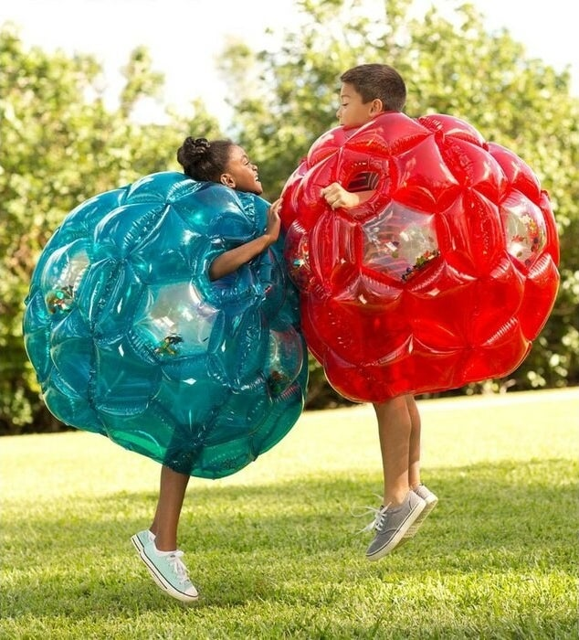 Two children in blue and red inflatable balls bump into each other