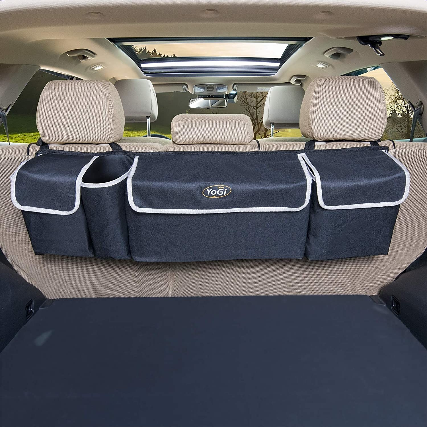 A navy blue with white piping storage organizer with three large pockets hanging from the backseat into a car's trunk