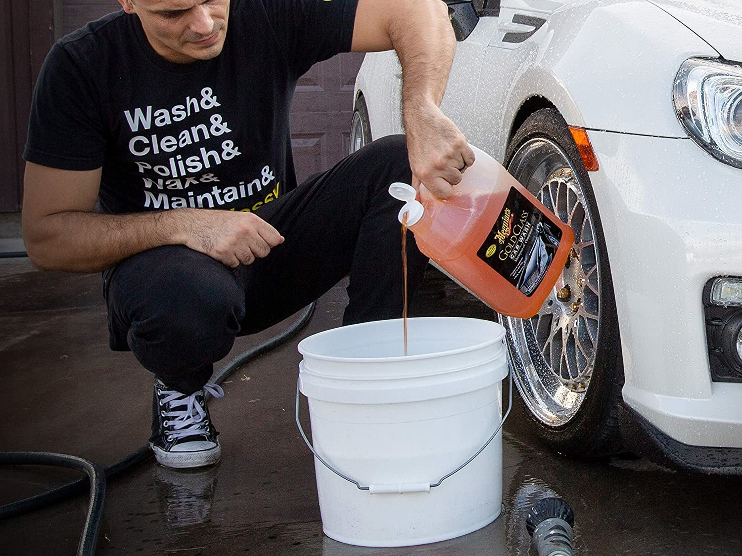 A person pouring car was liquid into a white bucket prepping to clean a white car