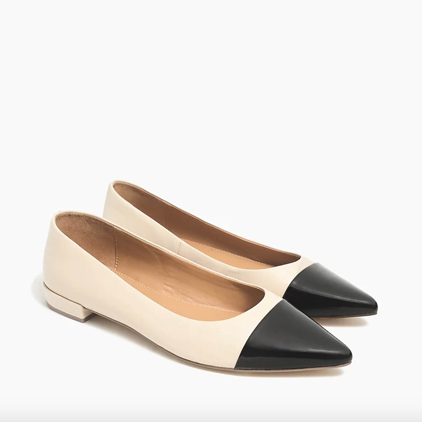 The flats, which have a nude body and a black pointed toe, against a plain background