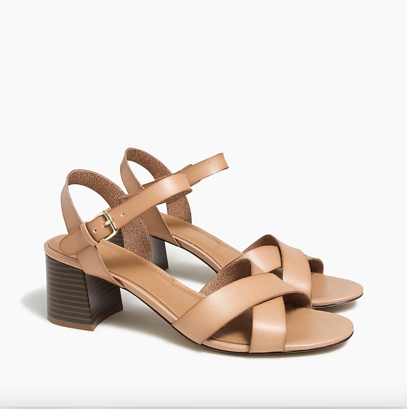 A pair of cross-strap low-block caramel brown heels against a plain background
